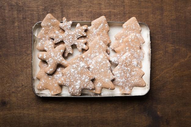 Weihnachtslebkuchenplätzchen verschiedene formen in platte auf holzraum