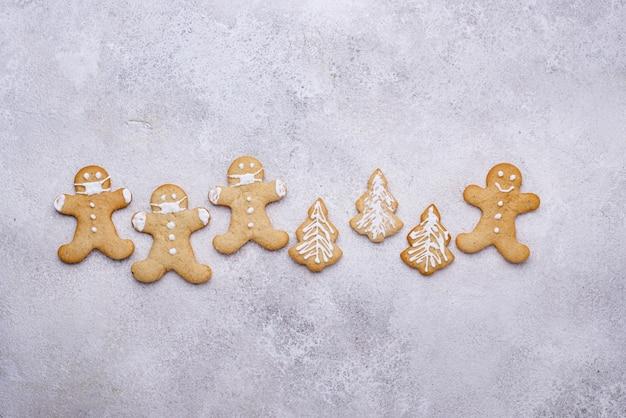 Weihnachtslebkuchenplätzchenmann in gesichtsmasken. soziales distanzkonzept