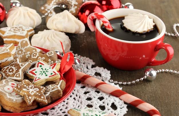 Weihnachtsleckereien auf teller und tasse kaffee auf holztisch nahaufnahme