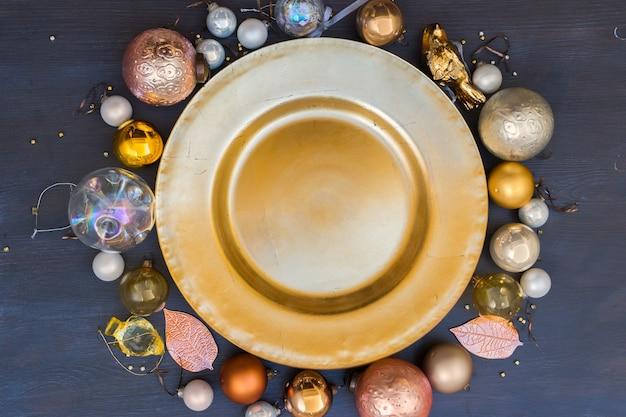 Weihnachtsleerer goldener teller mit goldkugeldekorationen