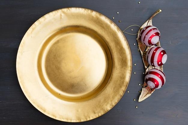 Weihnachtsleerer goldener teller mit roten dekorationen