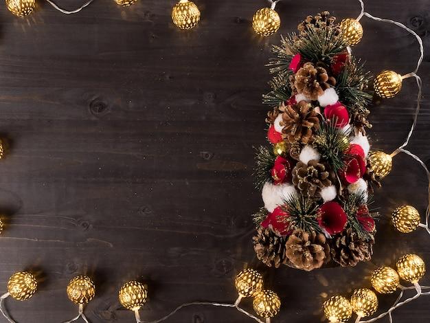 Weihnachtslicht auf hölzernem hintergrund mit hauptdekorationen. beleuchtung. weihnachtsbaum