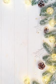 Weihnachtslichtbälle mit tannenbaumast und kegel auf weißem hölzernem, draufsicht copyspace