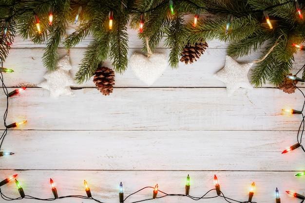 Weihnachtslichtbirne und kiefernblattdekoration auf weißem holzbrett