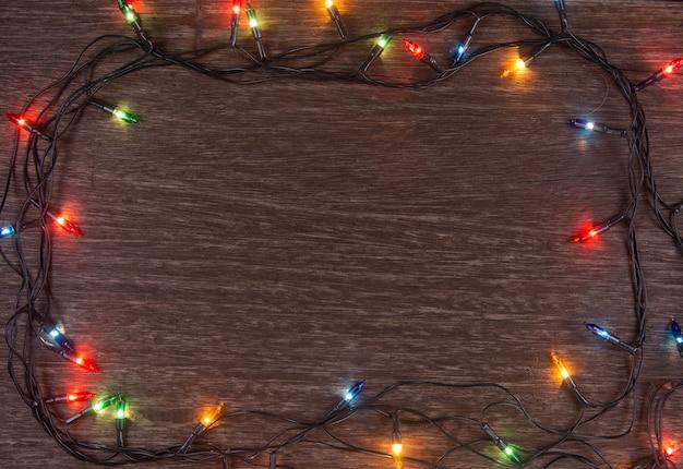 Weihnachtslichter auf dunklem hölzernem hintergrund. frohe weihnachten und ein glückliches neues jahr