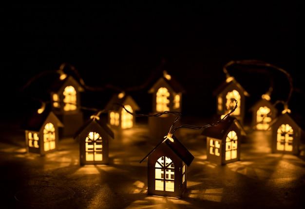 Weihnachtslichter innerhalb der hölzernen spielzeughäuser