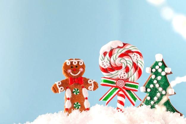 Weihnachtslutscher, weihnachtsbaum, ingwermann im schnee auf einer blauen oberfläche