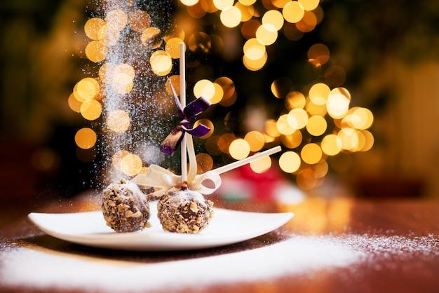 Weihnachtslutscherkuchen mit fallendem zucker auf einem teller.