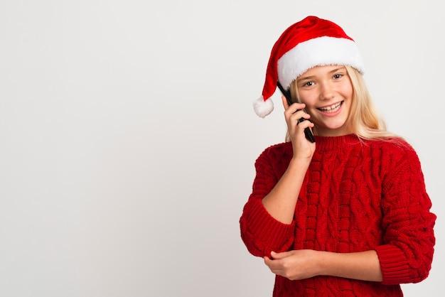 Weihnachtsmädchen, das am telefon spricht