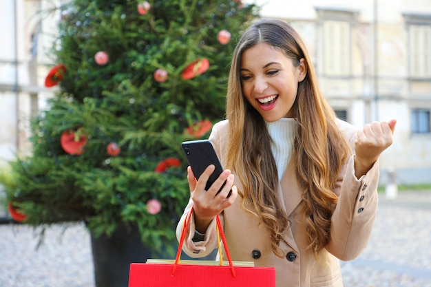 Weihnachtsmädchen. glückliche aufgeregte junge frau mit einkaufstüten in ihrer hand, die weihnachtsgeschenke mit ihrem smartphone draußen kaufend kauft.