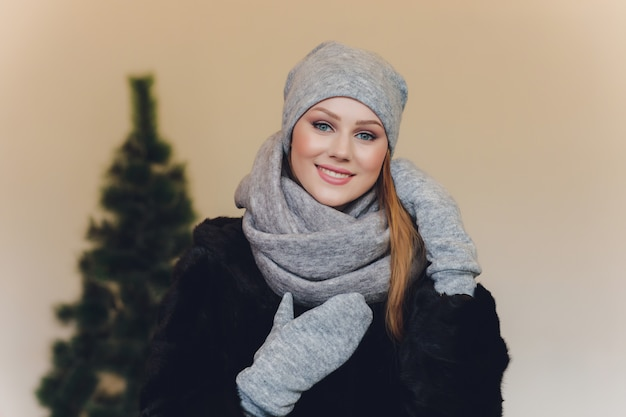 Weihnachtsmädchen, welches die gestrickte warme mütze und handschuhe, lokalisiert auf grau trägt
