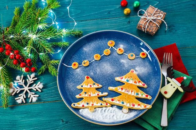 Weihnachtsmahlzeit für einen kinderpelzbaum geformte pfannkuchen auf dem teller