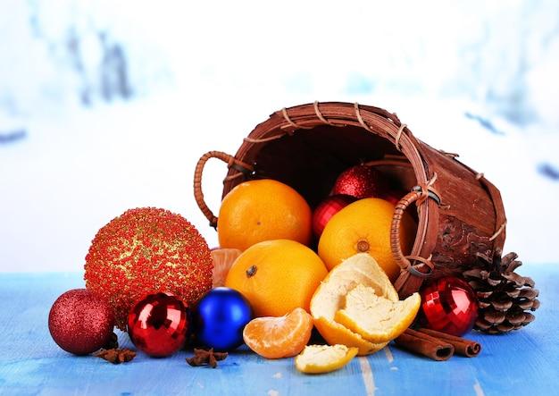Weihnachtsmandarinen und weihnachtsspielzeug auf holztisch auf schneehintergrund