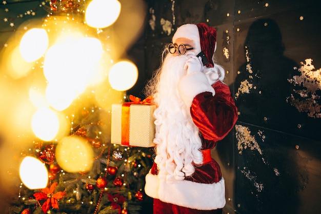 Weihnachtsmann, der am telefon spricht und ein geschenk hält