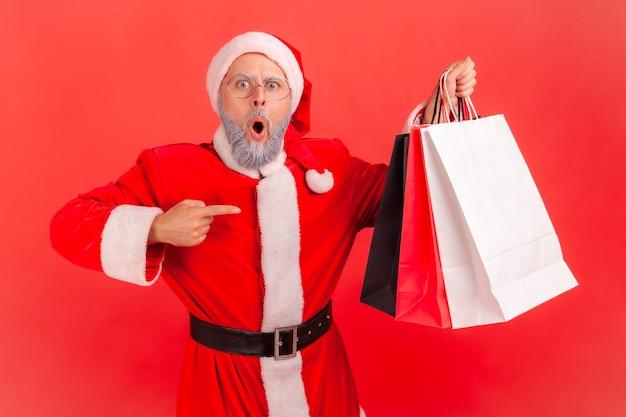 Weihnachtsmann, der auf einkaufstüten zeigt, beeindruckt vom kaufkauf zu niedrigen preisen.