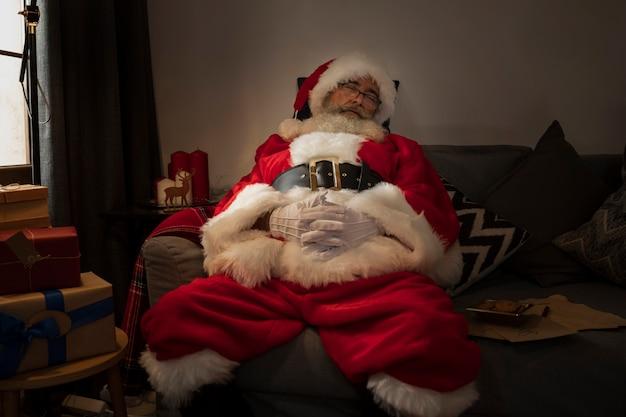 Weihnachtsmann, der auf sofa ein schläfchen hält