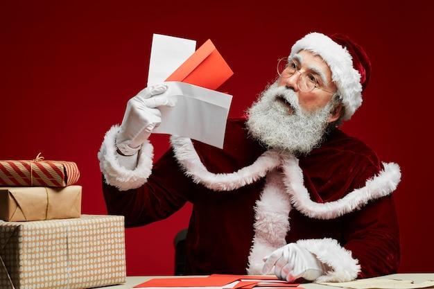 Weihnachtsmann, der buchstaben auf rot hält