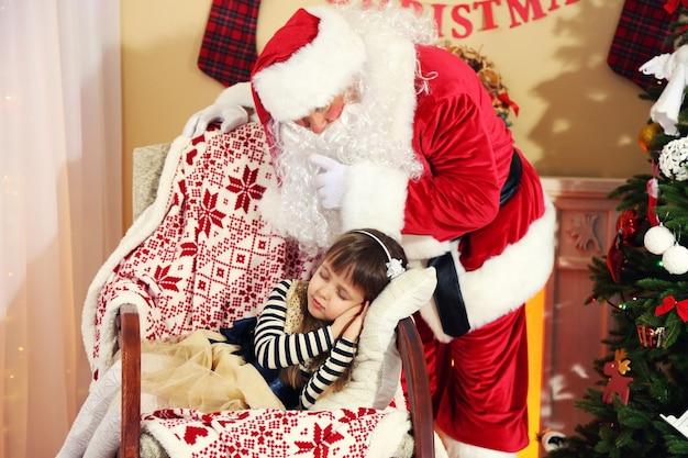 Weihnachtsmann, der dem schlafenden kleinen süßen mädchen weihnachtsbaum zu hause ein geschenk gibt