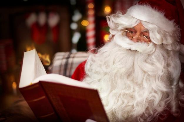 Weihnachtsmann, der die heilige bibel im innenraum liest