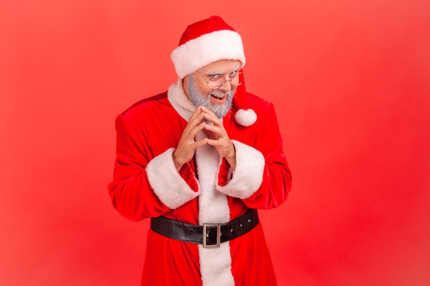 Weihnachtsmann, der die kamera mit listigem, kniffligem gesicht und grinsen betrachtet und einen bösen trick plant.