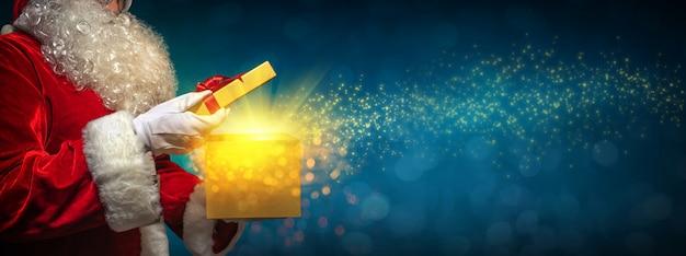 Weihnachtsmann, der eine geschenkbox weihnachten öffnet
