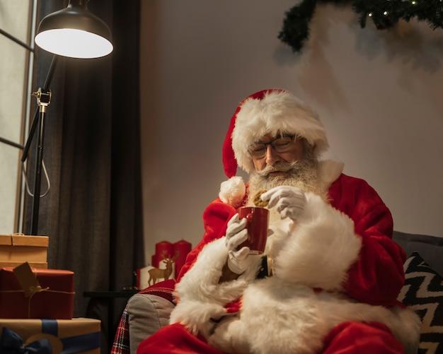 Weihnachtsmann, der eine heiße schokolade und ein plätzchen isst