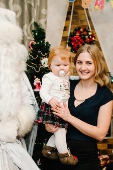 Weihnachtsmann, der einem kleinen baby mit mutter in der nähe des kamins und des weihnachtsbaumes zu hause ein geschenk gibt. snow maiden brachte kindern geschenke. neujahrskonzept. fröhliche weihnachten. ferien.