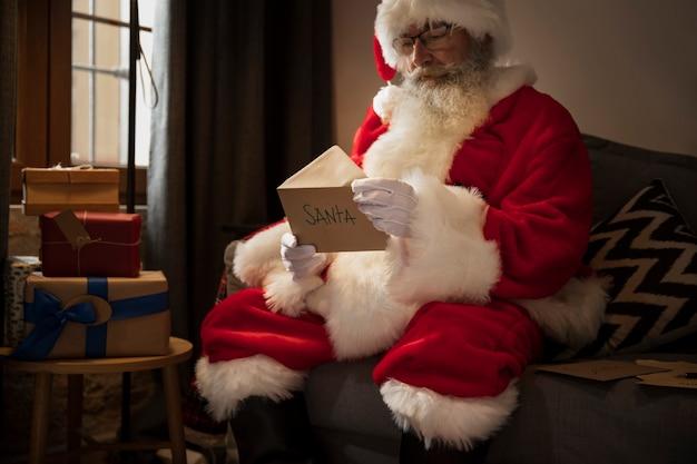 Weihnachtsmann, der einen brief von einem kind öffnet