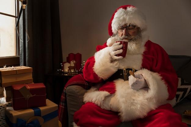 Weihnachtsmann, der einen tasse kaffee trinkt