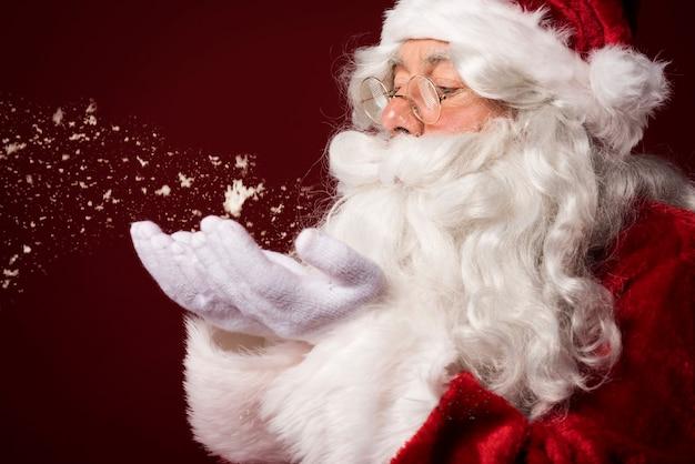 Weihnachtsmann, der einige schneeflocken bläst