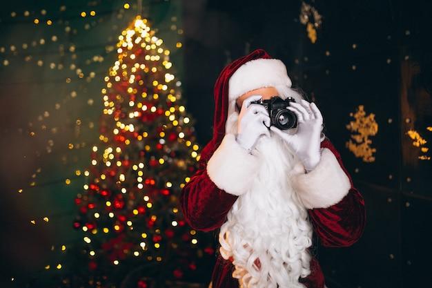 Weihnachtsmann, der fotos auf kamera macht