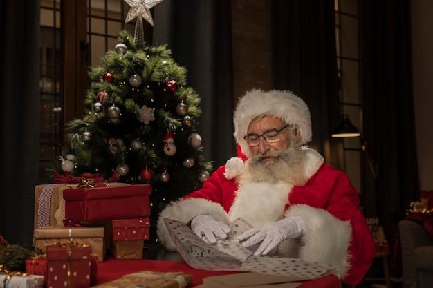 Weihnachtsmann, der geschenke einwickelt