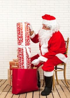 Weihnachtsmann, der geschenke für weihnachten vorbereitet