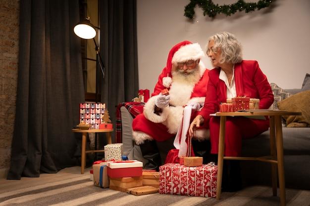 Weihnachtsmann, der geschenke mit frau einwickelt