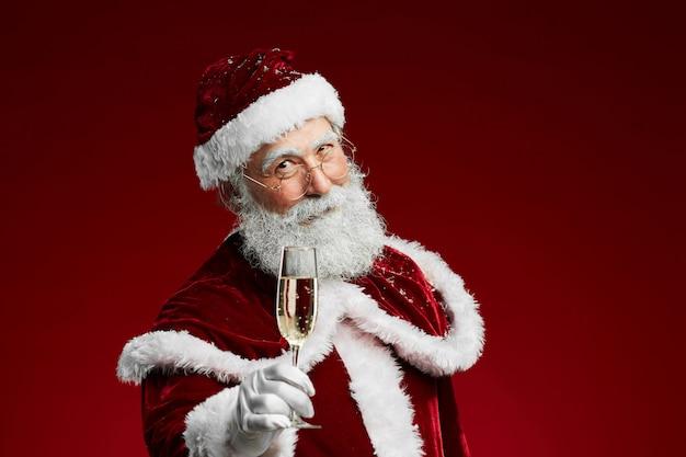 Weihnachtsmann, der glas champagner hält