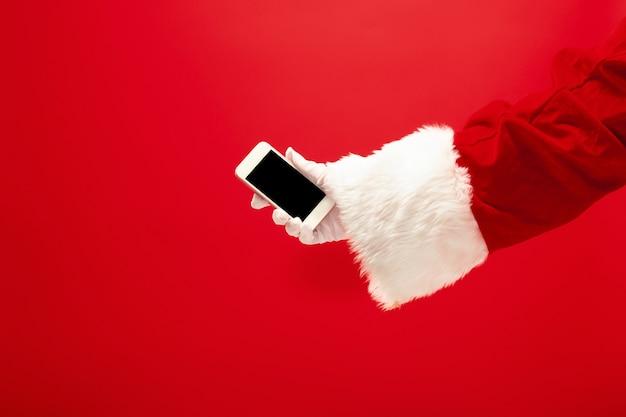 Weihnachtsmann, der handy bereit hält für weihnachtszeit auf rotem studiohintergrund. die jahreszeit, winter, feiertag, feier, geschenkkonzept