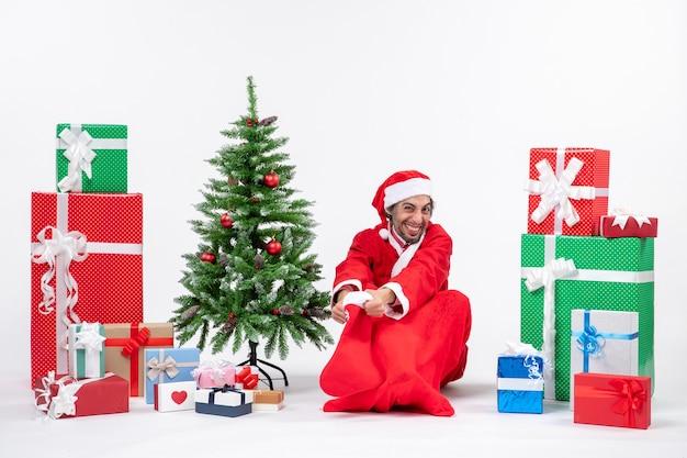 Weihnachtsmann, der im boden sitzt und weihnachtssocke nahe geschenken und geschmücktem baum hält