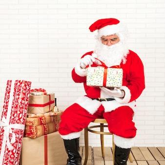 Weihnachtsmann, der in den händen anwesend sitzt und hält