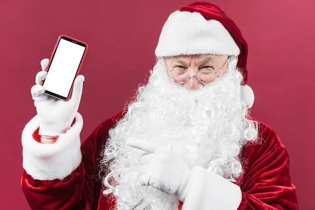 Weihnachtsmann, der in der hand telefon hält