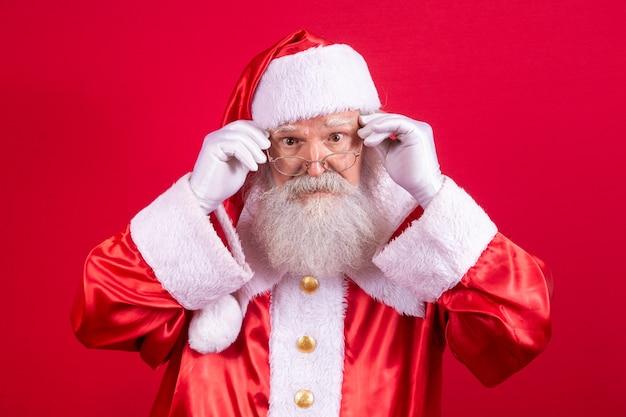 Weihnachtsmann, der in die kamera schaut. weihnachten steht vor der tür. frohe weihnachten. der weihnachtsmann schaut zu. hält seine brille.