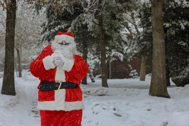 Weihnachtsmann, der in einer roten tasche geschenke für weihnachten um weißen schnee hält