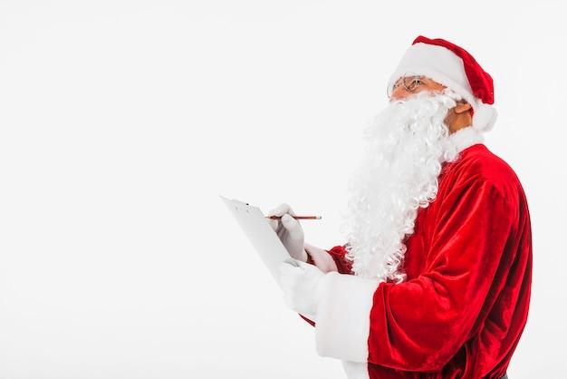 Weihnachtsmann, der in klemmbrett schreibt