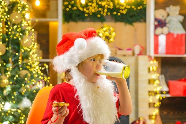 Weihnachtsmann, der keks und glas milch auf weihnachtsbaum hält