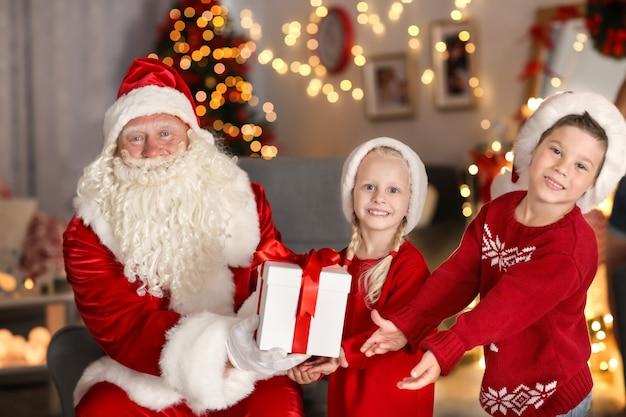 Weihnachtsmann, der kindern im zimmer mit schöner weihnachtsdekoration ein geschenk gibt