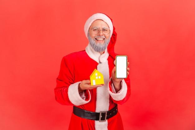 Weihnachtsmann, der kleines papierhaus und intelligentes telefon mit leerem bildschirm hält.