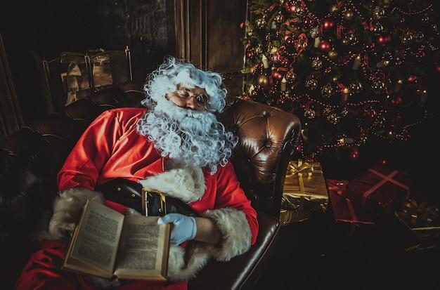 Weihnachtsmann, der mit buch auf händen schläft
