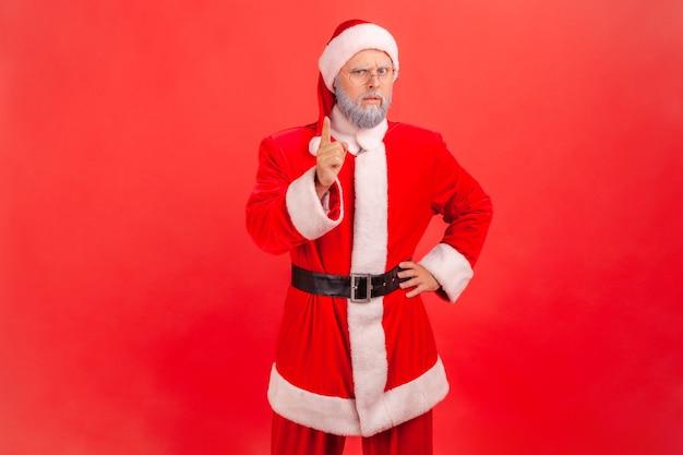Weihnachtsmann, der mit erhobenem zeigefinger steht und warnende geste zeigt, sei vorsichtig, ermahnender ausdruck.