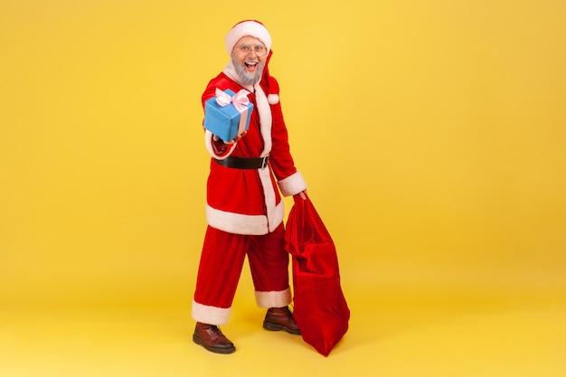 Weihnachtsmann, der mit roter tasche mit geschenken steht und weihnachtsgeschenkkasten heraushält.