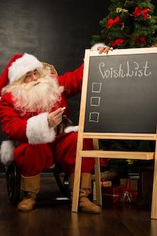 Weihnachtsmann, der nahe tafel sitzt
