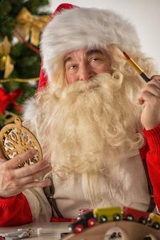 Weihnachtsmann, der neue spielwaren herstellt